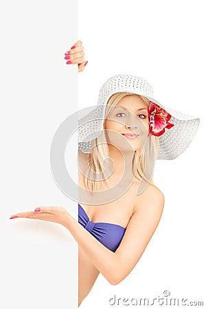 Femme de sourire dans le bikini se tenant et faisant des gestes sur un panneau