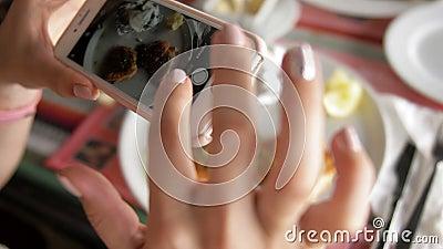 Femme de tourisme tenant à la main son smartphone et prenant la photo d'un mélange de poisson grillé sur une assiette blanche Pho clips vidéos