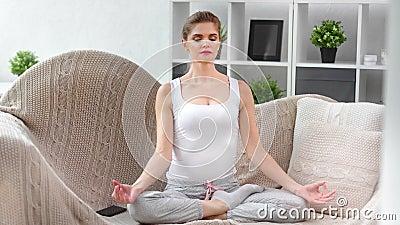 Femme domestique souriante pratiquant le yoga respirant assise sur un canapé à la maison clips vidéos