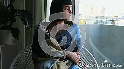 Femme enveloppée dans la couverture détendant dans le salon 4k banque de vidéos