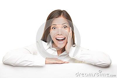 Femme Excited s appuyant sur le panneau blanc vide