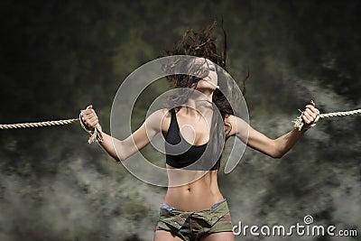 Femme forte avec les poignets attachés dans la robe sexy
