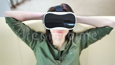 Femme heureuse en gros plan moyenne portant le masque et la détente modernes de réalité virtuelle banque de vidéos