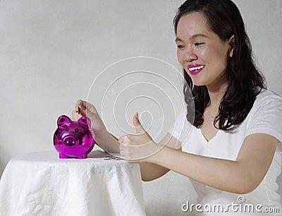 Femme mettant une pièce de monnaie dans la tirelire