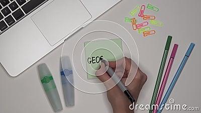 Femme réévaluant la GÉOGRAPHIE sur le bloc-notes, fin Ordinateur portable et papeterie sur la table banque de vidéos
