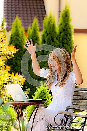 Femme réussie avec un ordinateur portatif dans le jardin