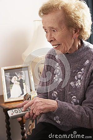 Femme aîné regardant la TV à la maison
