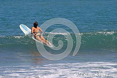 Femme s asseyant sur la planche de surfing