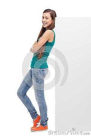 Femme se penchant contre le panneau-réclame blanc