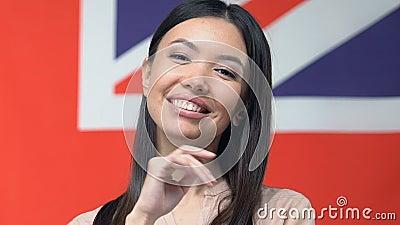 Femme souriante devant une caméra, isolée sur fond de drapeau britannique, agence de tourisme banque de vidéos