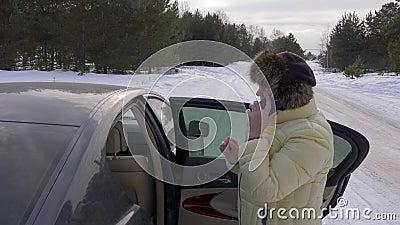Femme supérieure à l'aide du téléphone portable pour appeler tenir presque la voiture sur la route d'hiver banque de vidéos