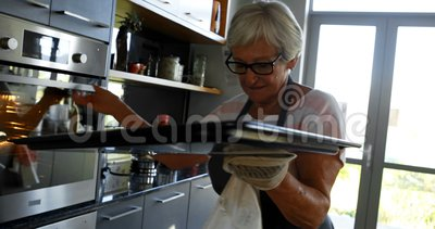 Femme supérieure enlevant le plateau de biscuit du four 4k banque de vidéos