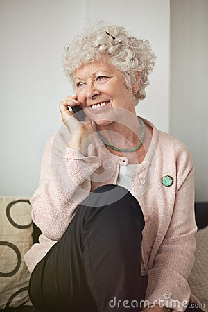 Femme supérieure heureuse au téléphone