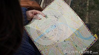 Femme tenant la carte entre les mains Touriste à la recherche de la destination sur une carte papier, pointant vers les lieux Fer banque de vidéos