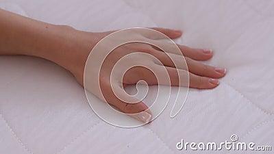 Femme touchant le matelas essayant la douceur, le choix du mobilier, la qualité du produit clips vidéos