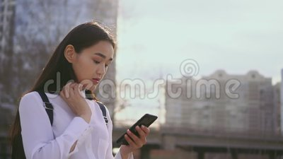 Femmina attraente facendo uso del telefono cellulare al rallentatore La ragazza raddrizza i suoi capelli archivi video