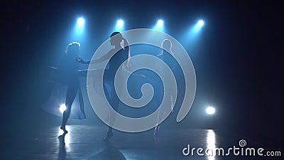 Femmine sensuali dei ballerini che ballano sopra i riflettori dello studio Movimento lento video d archivio