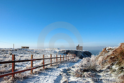 Fenced walk to ballybunion castle in winter snow