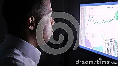 Fermez-vous d'un jeune et occup? homme d'affaires africain travaillant sur l'ordinateur la nuit clips vidéos