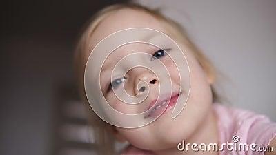 Fermez-vous d'un visage mignon de fille de petite blonde espiègle Fille clignotant ses yeux et sourire Projectile de verticale clips vidéos