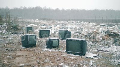 Fernseher, die während des Schnees auf eine Müllhalde geworfen werden stock footage