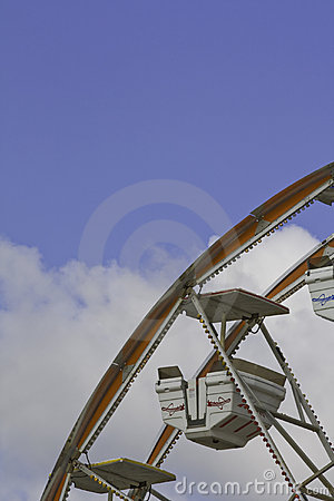 Ferris wheel car against a blue and white sky