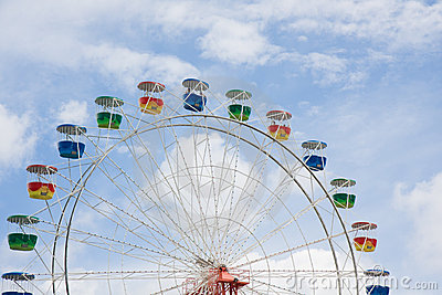Ferris wheel with clouds and blue sky