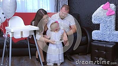 Festeggiamenti per il primo compleanno di una bambina con i suoi genitori a casa seduti sul divano archivi video