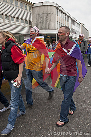 Festival goers hold hands and the rainbow banner Editorial Stock Image