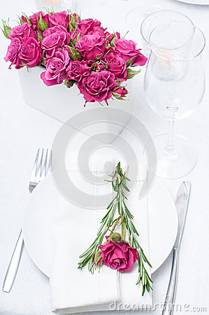 Festive dining table setting with pink roses