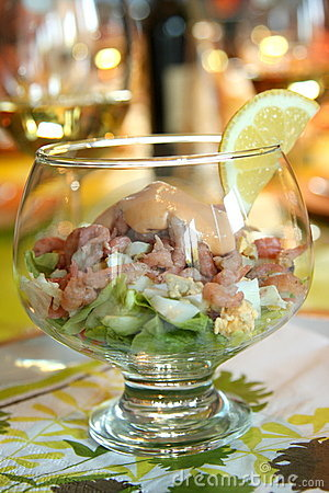 Shrimp salad with cocktail sauce and lemon on a festive table with ...