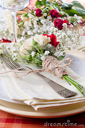 Festive table setting with flowers and vintage crockery, closeup