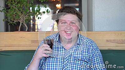 Fet lycklig man som rymmer ett exponeringsglas av läskcola och skrattar som sitter i kafé beverly stock video
