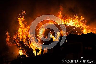 Fiamma bruciante del fuoco sul tetto di legno della casa for Piani della casa sul tetto