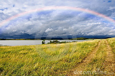 Field road and rainbow over lake