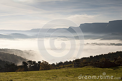 Fields and mountains on a cold morning, fog in the valley and clouds in the sky