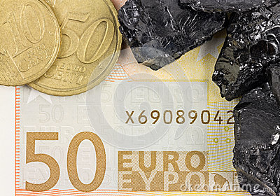 Fifty euro banknote with euro coins and raw coal nuggets