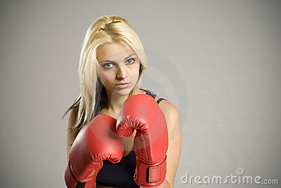 Fighting woman boxer with red gloves