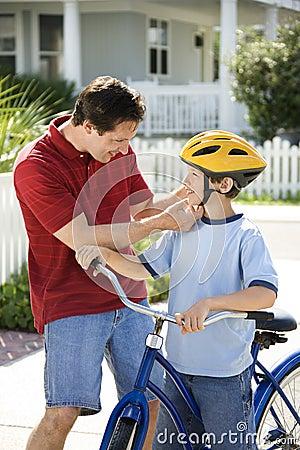 Figlio d aiuto del papà con il casco