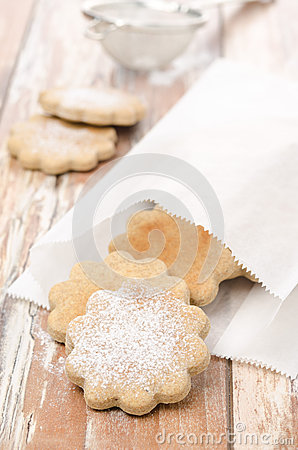 Figured cookies sprinkled with powdered sugar in a paper bag