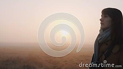 Fijne bedachtzame mooie blanke toeristenvrouw die langs een prachtige roze bruine zonneschijn-uitzichtveld loopt langzame bewegin stock videobeelden