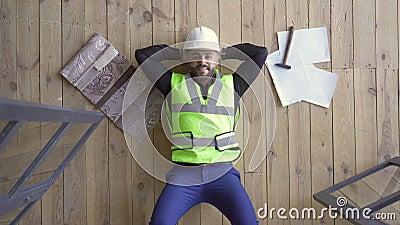 Fijne bouwer in de helm en het groene jasje dat op de vloer ligt en omhoog kijkt Hammer en tekeningen die naast hem liggen De stock video