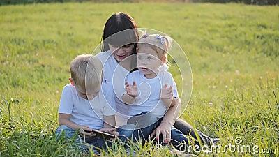 Fijne familie, moeder en kinderen hebben plezier in de buitenlucht in Park Een groep kinderen broer en zus die een smartphone geb stock footage