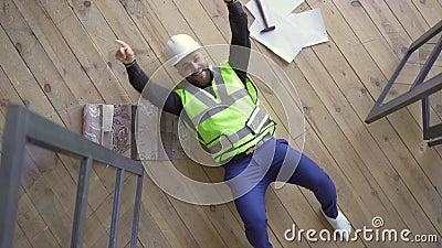 Fijne glimlach in de helm van de bouwer en het groene jasje dat op de vloer ligt, die de overwinningsgebaren toont en omhoog kijk stock videobeelden
