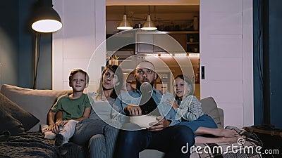Fijne jonge Kaukasische familie met twee kinderen kijken naar film en praten thuis op de bank samen Entertainment-concept stock video