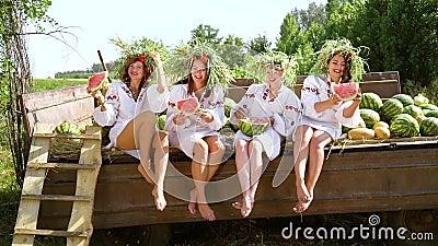 Fijne meisjes in folklore kostuums die watermeloenen eten in de aanhangwagen stock footage