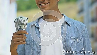 Fijne tiener die een bundel dollars toont, geld bespaart voor droom, loterij wint stock footage