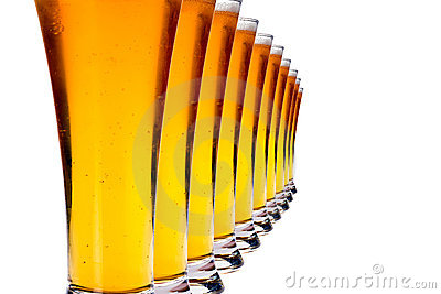 Fila de vidrios con la cerveza de cerveza dorada