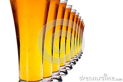 Fileira dos vidros com cerveja de lager