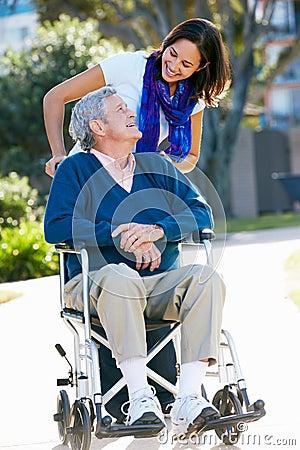 Filha adulta que empurra o pai sênior na cadeira de rodas